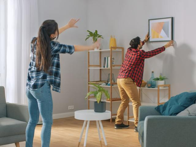 Woman instructing man how to hang a picture
