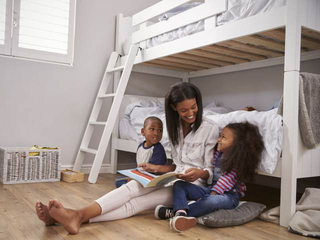 Mom with two kids leaning on bunk bed