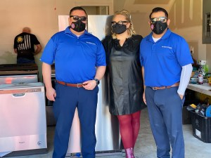 Two men and one woman in the middle wearing masks standing together for photo