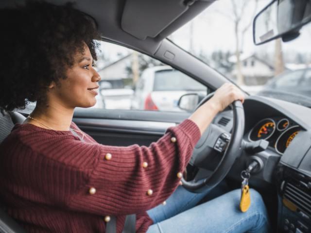 Woman in car holding steering wheel