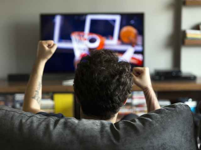 Man sitting on couch excitedly watching a basketball game.