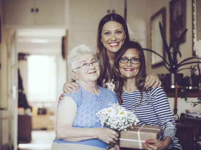 Three generations of women smiling at camera.