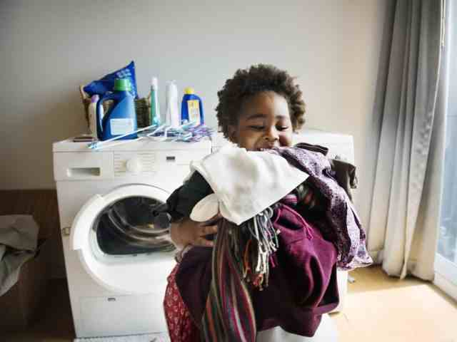 Child carrying laundry from dryer.