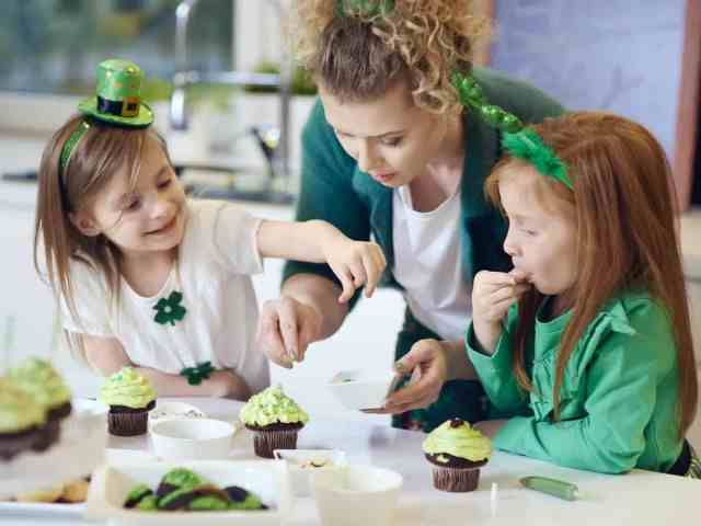 A mother and two young daughters dressed in green and decorating St. Patrick's Day cupcakes