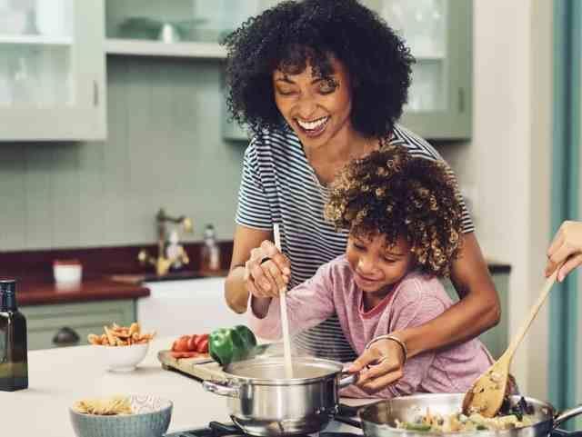 Mother and child cooking pasta meal together on stove.