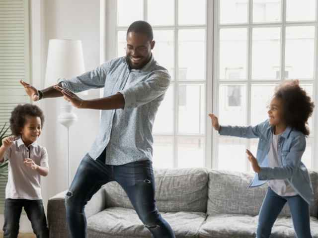 A father and his two children dancing in living room together.