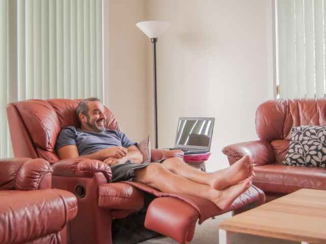 Smiling man sitting in clay colored recliner with feet up.