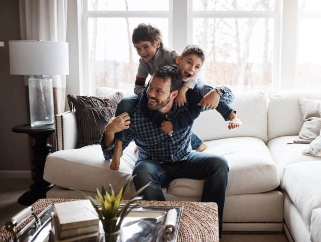 A man on a cream colored sectional plays with his two sons as they jump on his back.