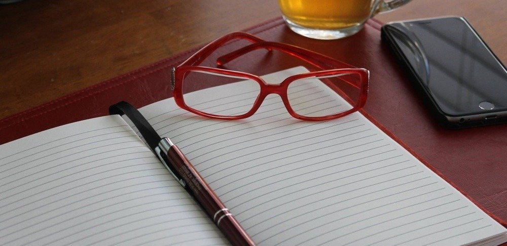 glasses, pen, and notebook
