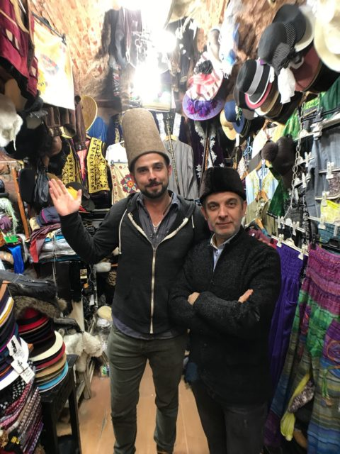 man wearing traditional turkish hat in a store surrounded by hats with the hat seller