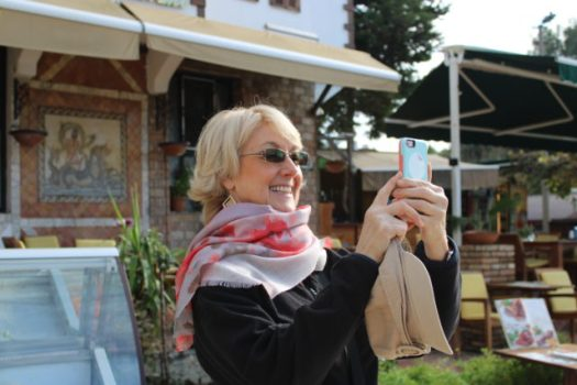 smiling woman taking a photo on her phone