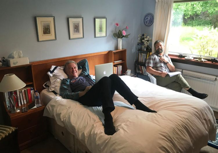 rick steves sitting on a bed in a hotel room with a laptop on his lap and simon griffith sitting in a chair next to him