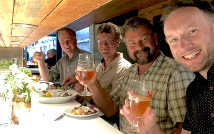 colin mairs, simon griffith, karel bauer, and rick steves smiling at a restaurant bar and holding beverages
