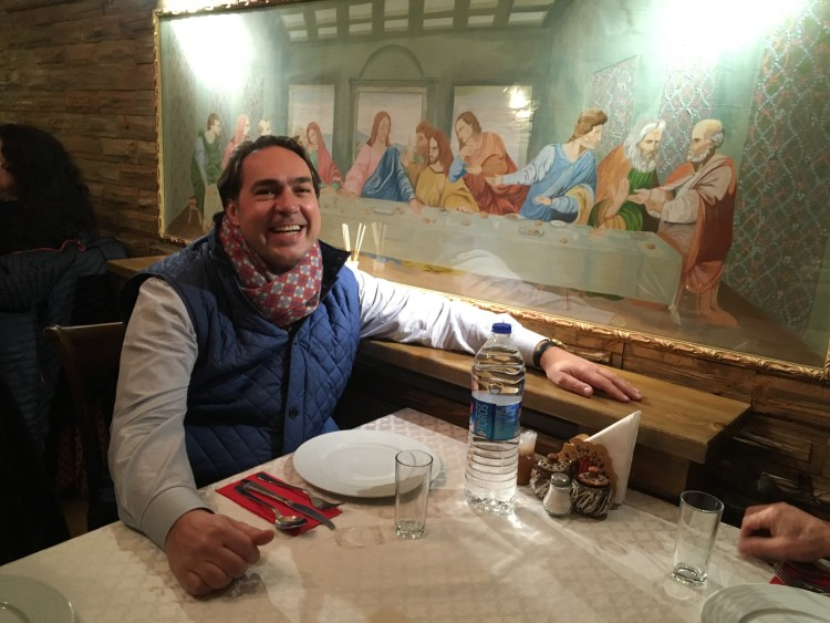 tour guide apostolos douras smiling and sitting in a restaurant booth