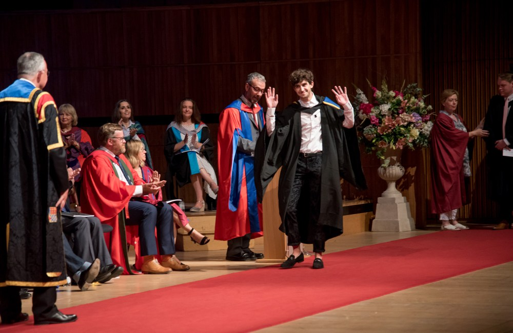 A student literally dancing for joy as he goes to accept his degree
