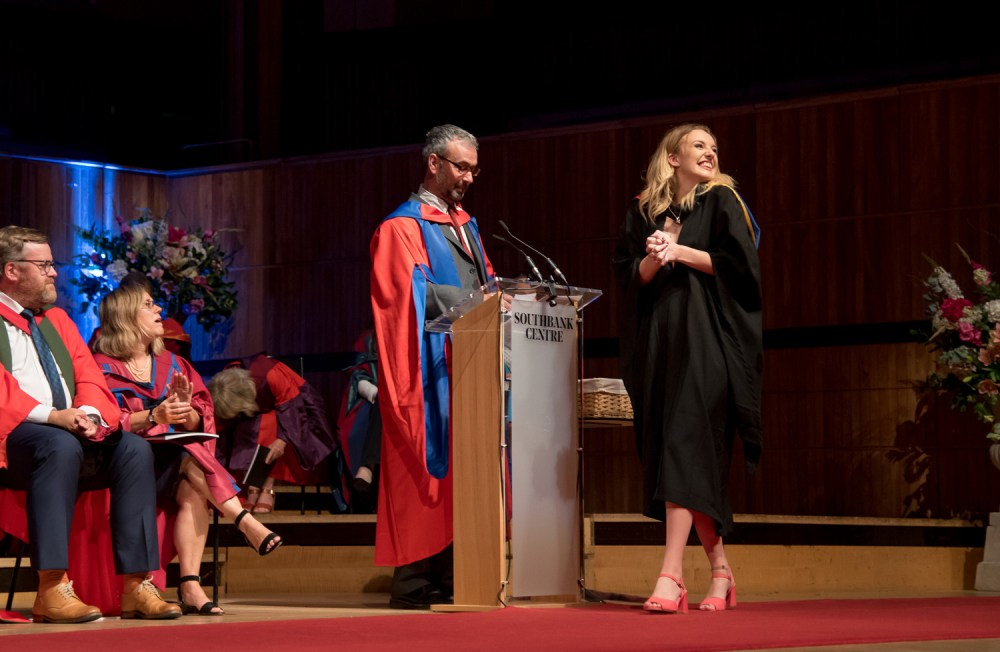 A conspicuously happy student accepts her degree