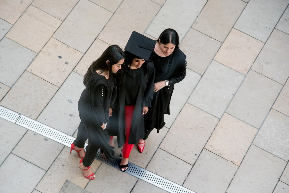 Three graduates pose for a photo together