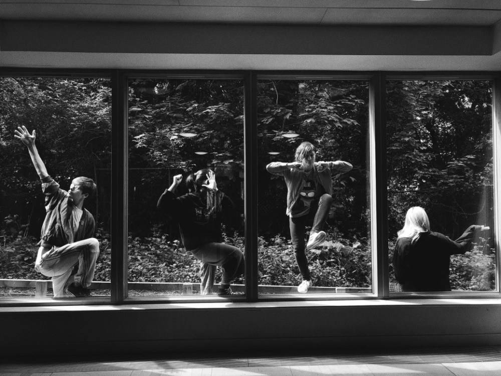 Students dance beyond the windows of a studio
