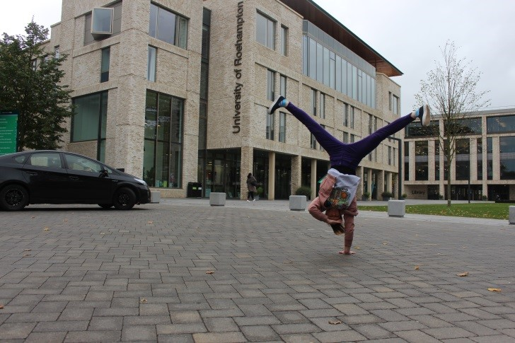 A student performs a handstand outside the Library