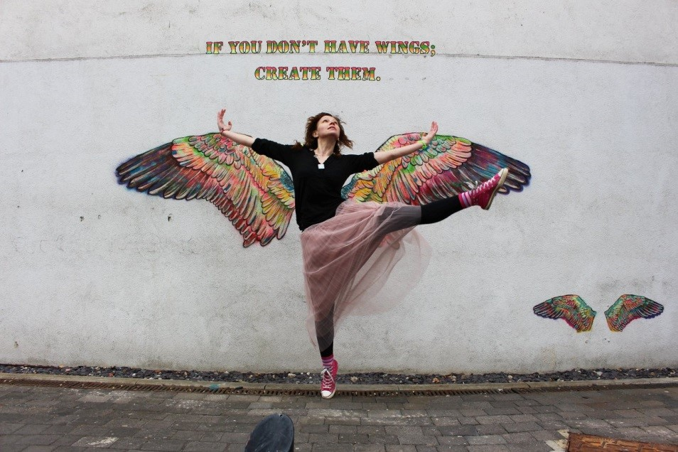 Olga in front of Gisella Stapleton's 'Wings' mural