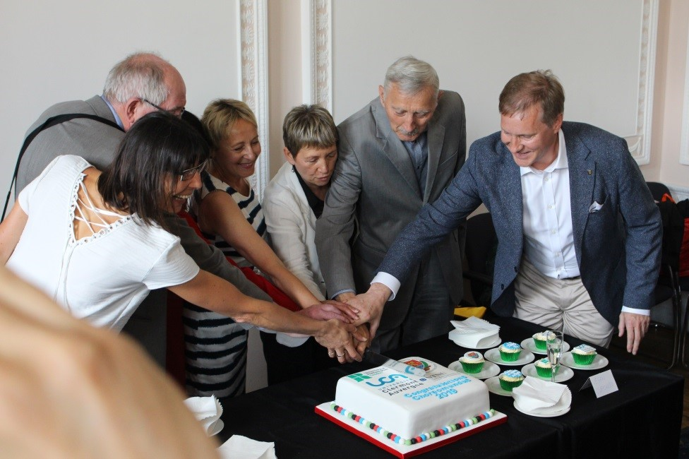Representatives of the partner universities cutting a cake