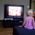 Little girl in front of a big TV