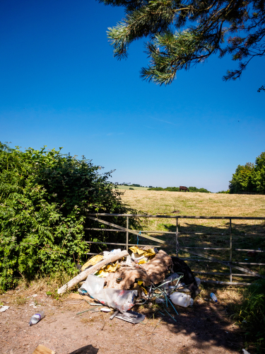 Beautiful sunny landscape with dumped waste against a gate