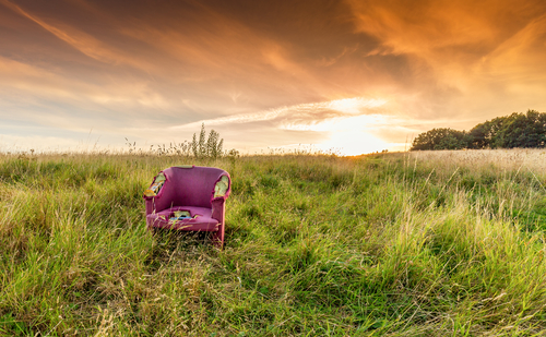 Abandoned chair amidst a sunny background, fly tipping image