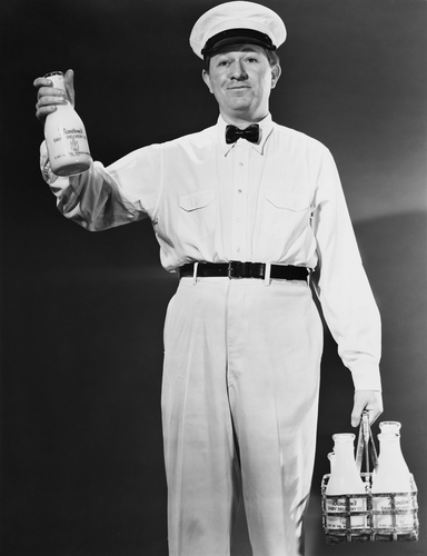 Milkman holding bottles of milk to be delivered (black & white image)