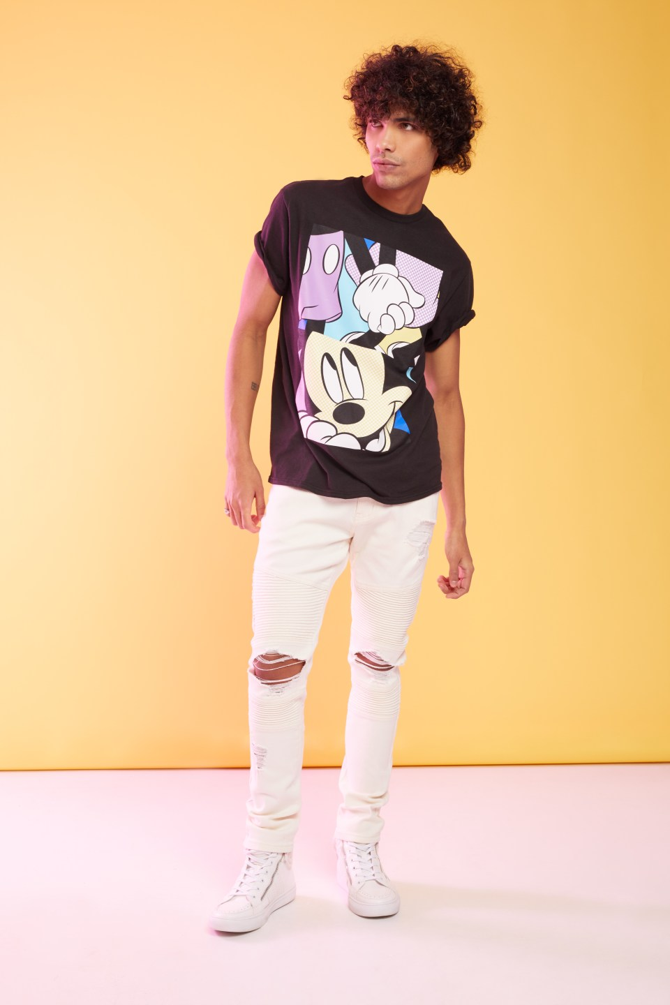 A male model wearing a Mickey Mouse Graphic tee with ripped skinny jeans and sneakers.