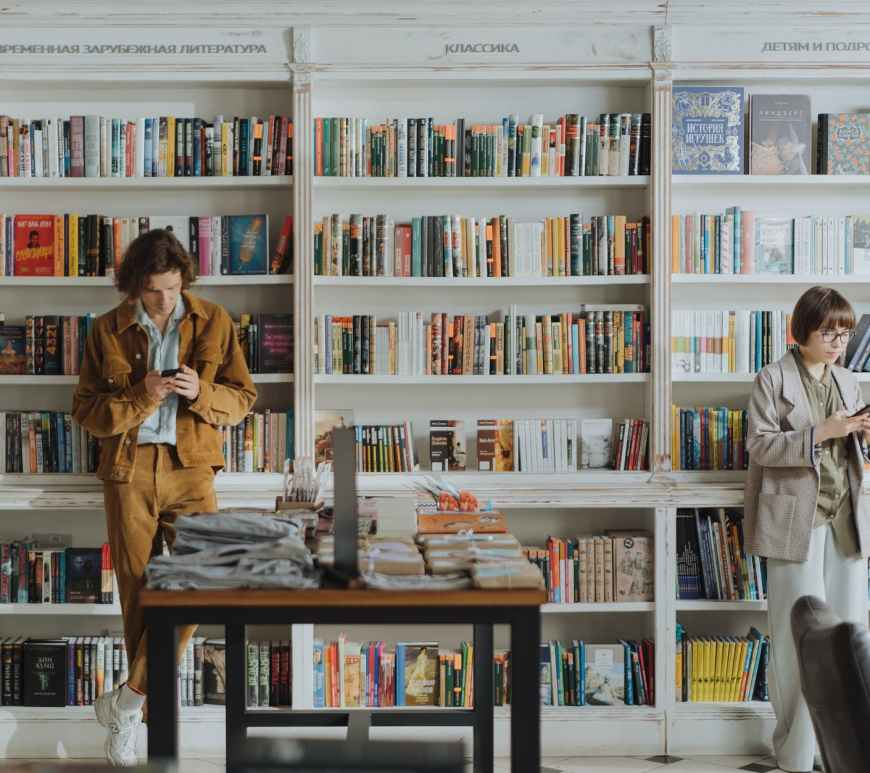 woman in brown coat standing in front of books