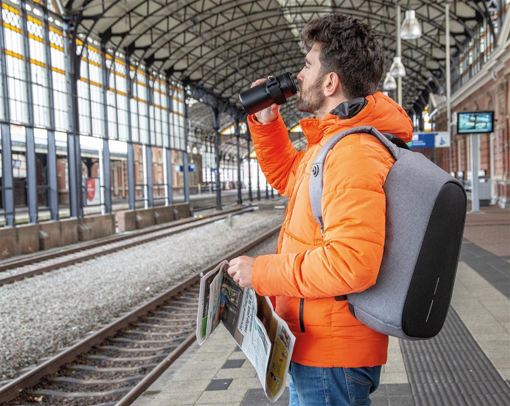 Uomo in stazione con zaino personalizzato