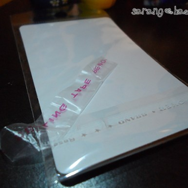 """Back of one of the cards - all are blank sticker paper backs. Random bit of loose tape says """"Sealing tape remove""""."""
