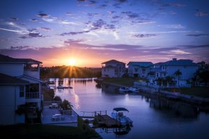 Florida canal at sunset surrounded by waterfront homes, boats, and docks.