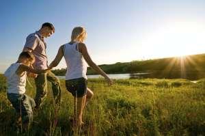 A family walking through an open grass field.