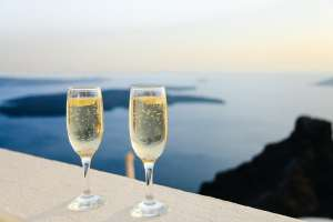 Two glasses of champagne with an ocean view in the background.