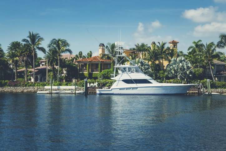 A luxury Florida home with a yacht out front.