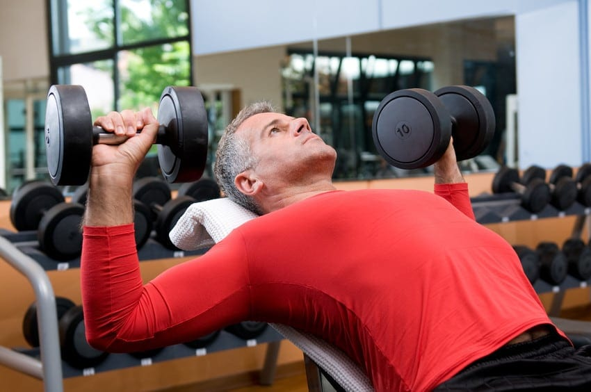 Older man lifting dumbell weights at the gym.