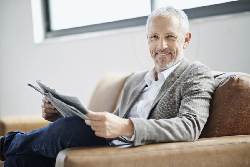 An older man holding a newspaper in his hands while he sits on a couch.