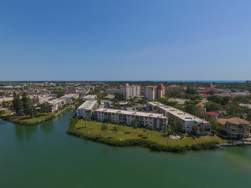 Front view of a condominium building overlooking the water.