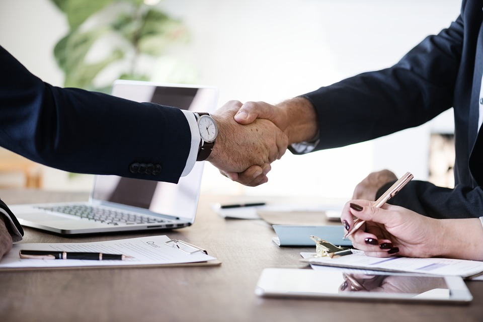 Two professionals shaking hands over a real estate deal, selling during the holiday season.