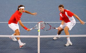 Federer and Wawrinka of Switzerland returns the ball to Johansson and Aspelin of Sweden during their men's doubles final tennis match at the Beijing 2008 Olympic Games,