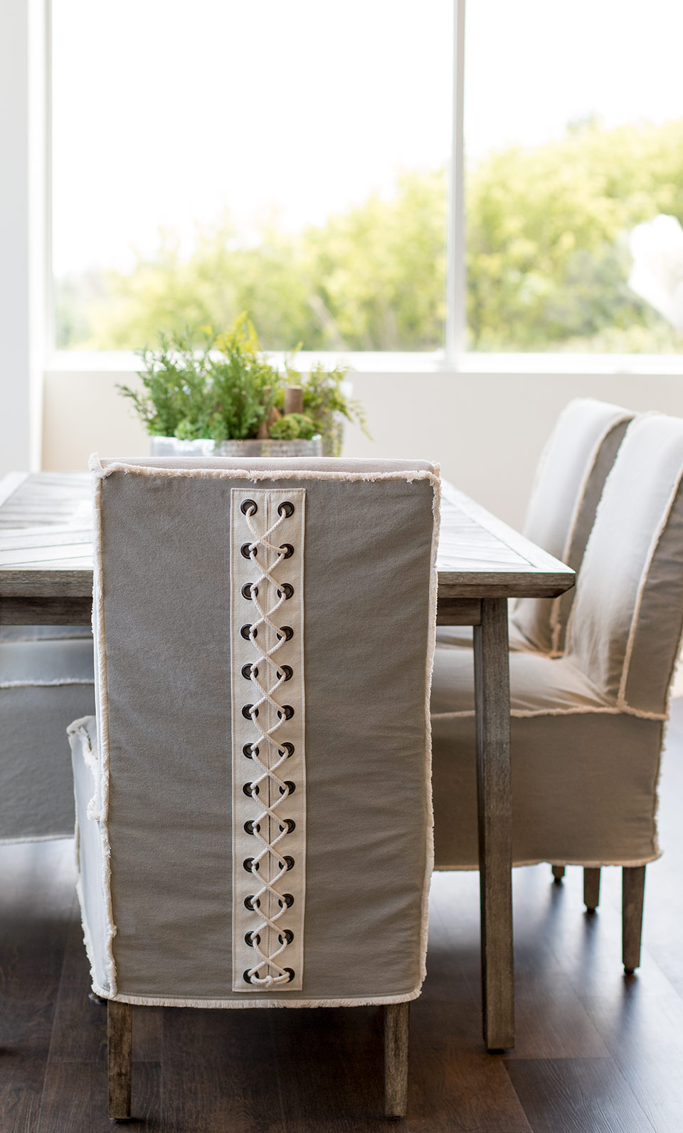Light and airy dining room - the slipcovered dining chair with decorative lacing adds personality and a unique decorating touch!