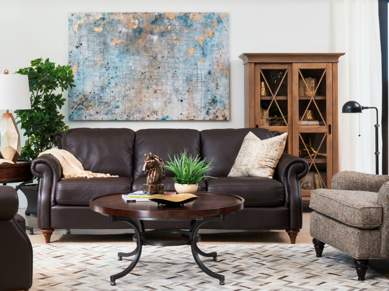 Living room with white walls, layered sisal and cowhid rugs, brown leather sofa - Schneiderman's Furniture