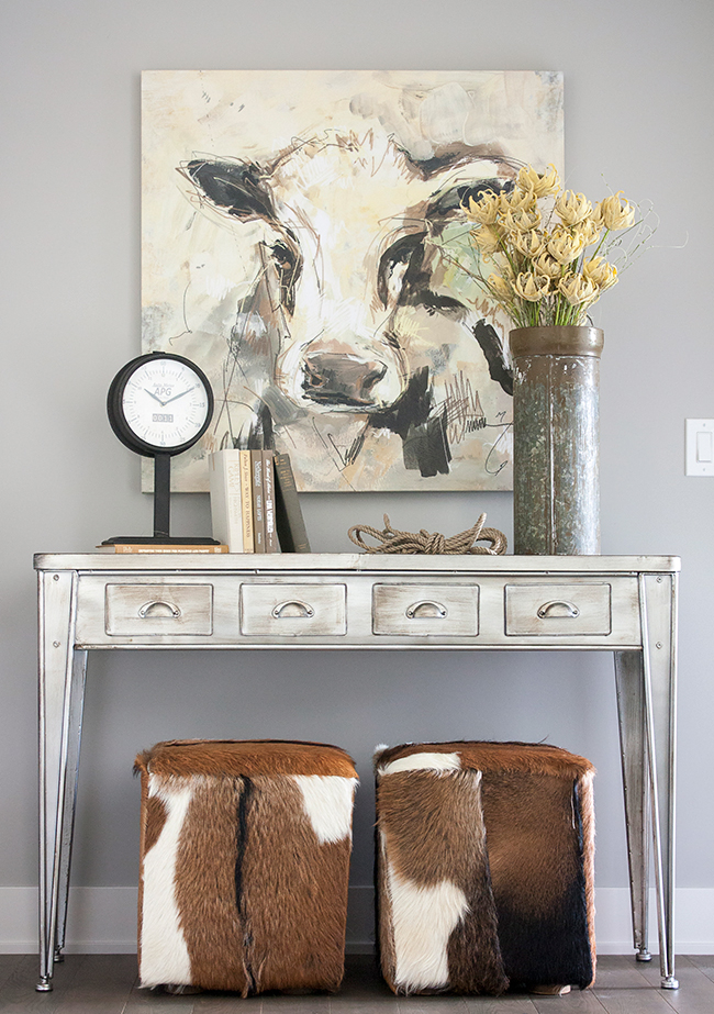 A whimsical and welcoming foyer. Gray walls, metal console table, cowhide ottomans, styling.