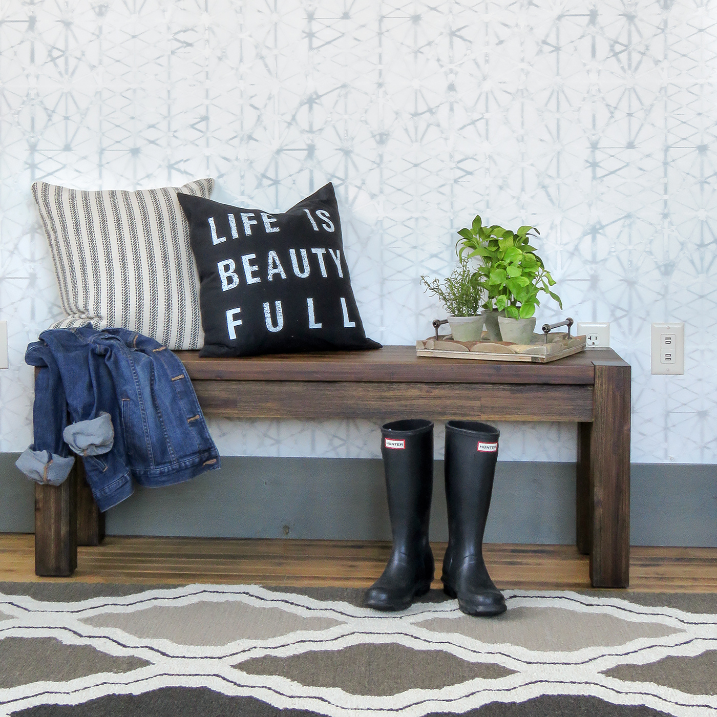 Fun idea for spring entry or foyer - love it! gray, black and white geometric rug, bench, gray and white wallpaper,