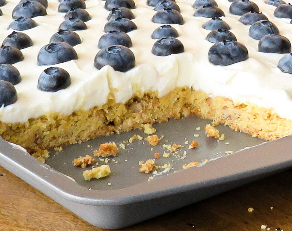lemon bars with pecans and graham crackers, topped with cream cheese frosting and blueberries