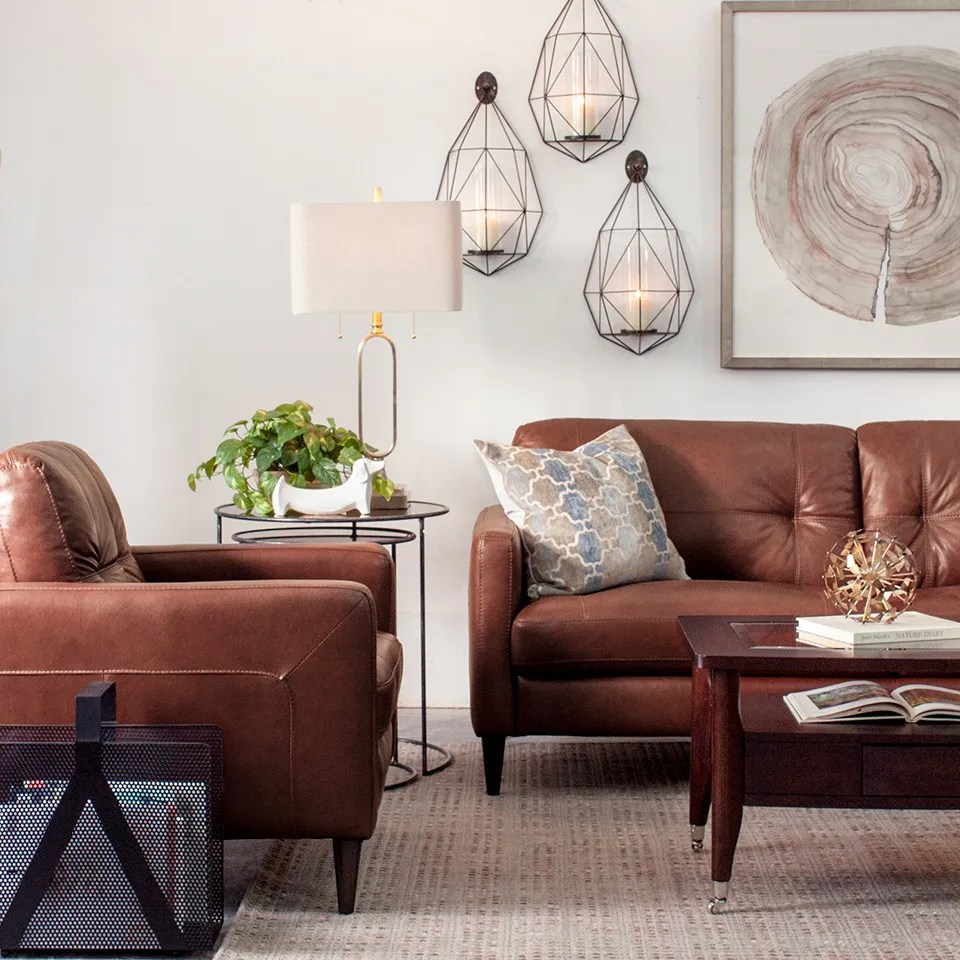 Living room with modern brown leather furniture white walls gold accents