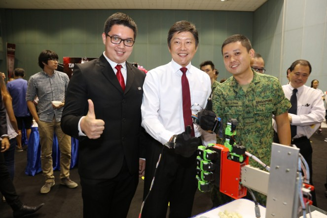 MIN joining Tham Jia Xiong and Woo Yi Jie (Merit Award Winner from ITE College Centre) with a thumbs up (the gesture was adapted real-time by their 'Generic Robotic Hand Control System' invention)