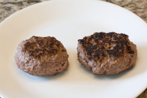 Two plain burger patties on a plate